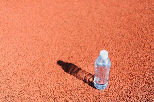 Bottiglia di acqua di plastica sulla pista da corsa