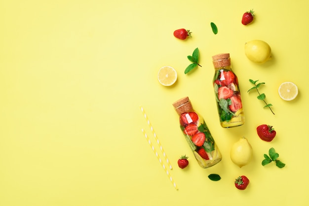 Bottiglia di acqua disintossicante con menta, limone, fragola. limonata di agrumi la frutta estiva ha infuso acqua.