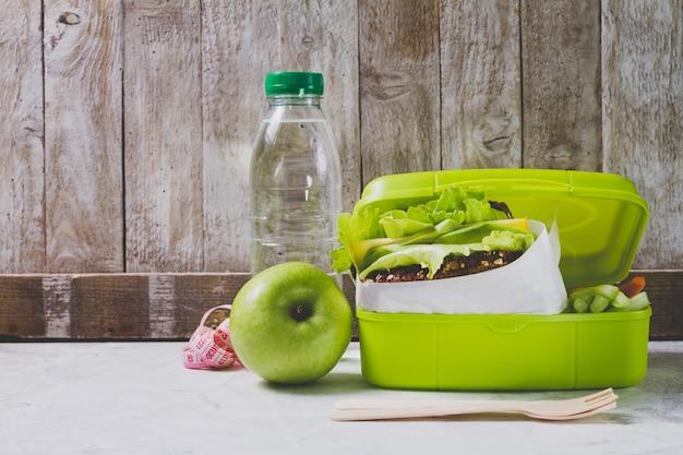 Bottiglia di acqua e mela accanto ad una scatola di pranzo