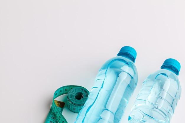 Bottiglia di acqua ed attrezzatura di forma fisica isolate su bianco