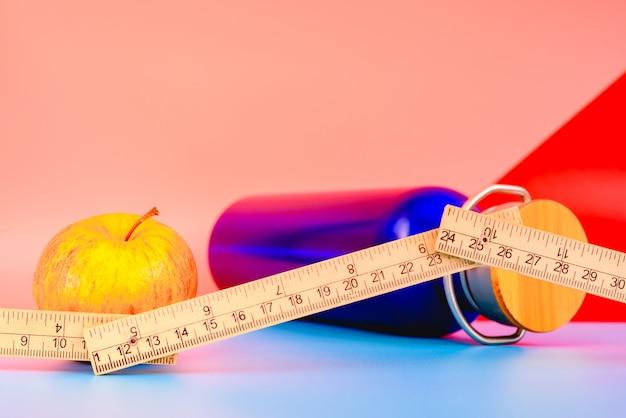 Bottiglia di acqua, mela e nastro di misurazione isolati su fondo variopinto in studio, concetto di vita sana.
