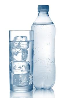 Bottiglia di acqua minerale e vetro con cubetti di ghiaccio isolato