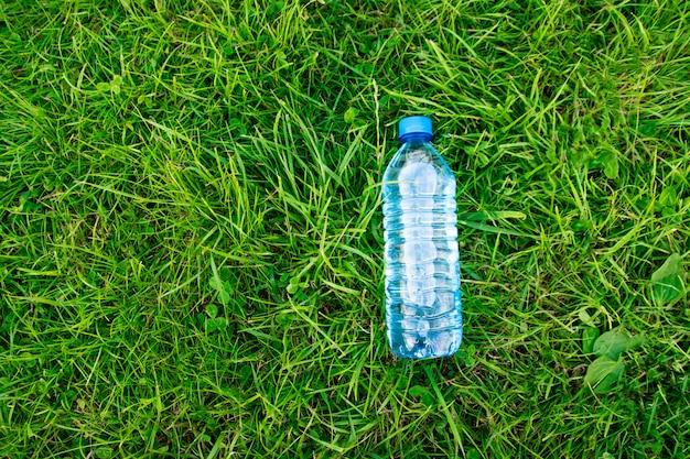 Bottiglia di acqua sull'erba verde. erba e prato in plastica. luce naturale. erba morbida e spessa.