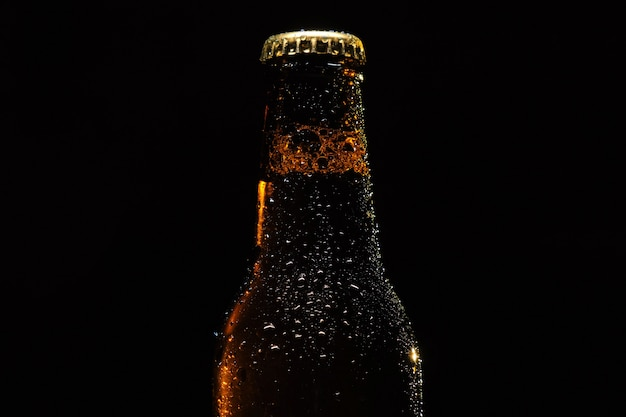 Bottiglia di birra con gocce di acqua primo piano su uno sfondo nero isolato.