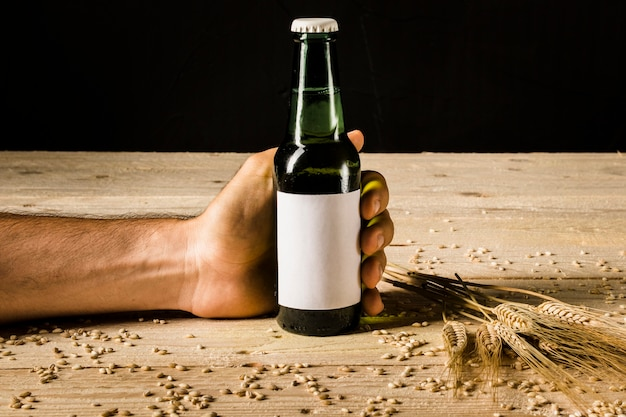 Bottiglia di birra della tenuta della mano dell'uomo con le orecchie di grano su superficie di legno