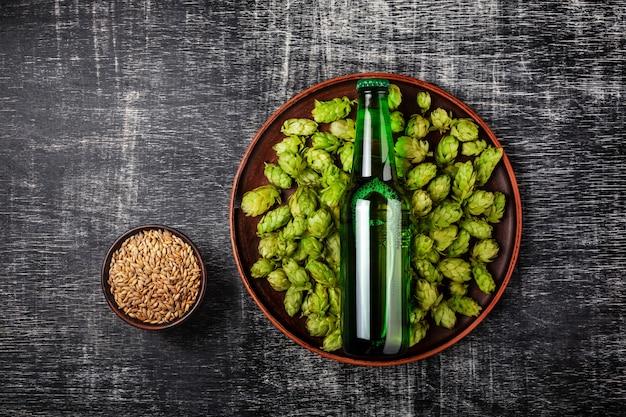 Bottiglia di birra su un luppolo fresco verde in un piatto con il chicco di avena contro lo sfondo di una lavagna graffiata nera