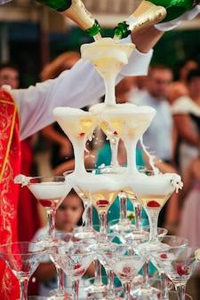 Bottiglia di champagne che viene versato in una piramide di vetro