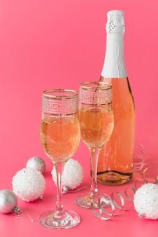 Bottiglia di champagne con bicchieri e palle di natale