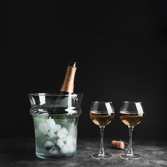Bottiglia di champagne con bicchieri sul tavolo
