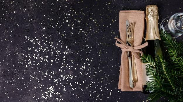 Bottiglia di champagne con decorazioni natalizie su sfondo scuro