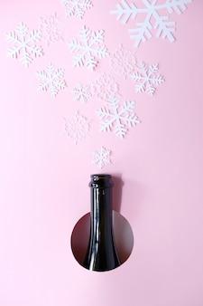 Bottiglia di champagne con differenti fiocchi di neve di natale sul rosa