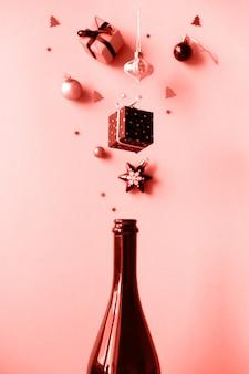 Bottiglia di champagne con diverse decorazioni natalizie sul rosa.