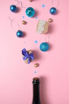Bottiglia di champagne con diverse decorazioni natalizie sul rosa