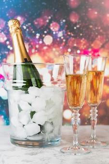 Bottiglia di champagne con ghiaccio e bicchieri
