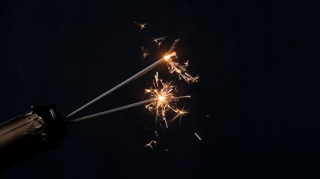 Bottiglia di champagne con lo sparkler bruciante del fuoco su fondo nero