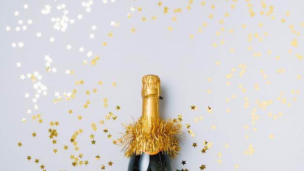 Bottiglia di champagne con lustrini a forma di stella