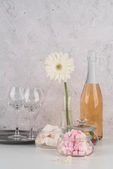 Bottiglia di champagne con marshmallow sul tavolo