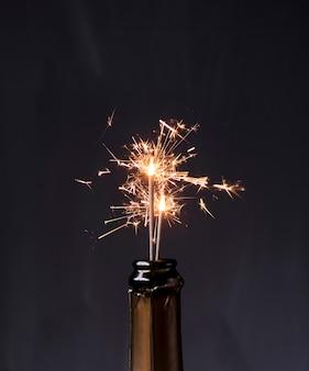 Bottiglia di champagne con stelle filanti su sfondo nero