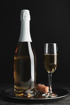 Bottiglia di champagne con vetro su un vassoio