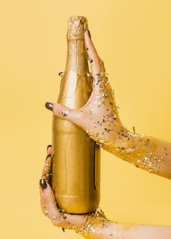 Bottiglia di champagne dorata tenuta in mano