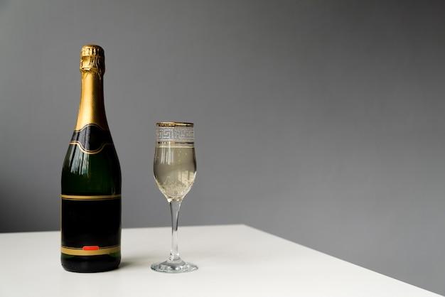 Bottiglia di champagne e bicchiere di champagne sul tavolo bianco