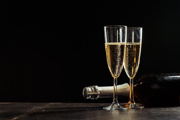 Bottiglia di champagne e bicchieri su sfondo scuro