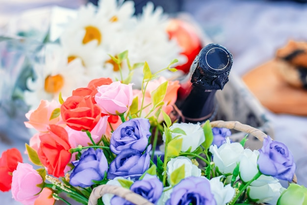 Bottiglia di champagne e bouquet di fiori di rose