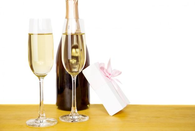Bottiglia di champagne e due bicchieri con confezione regalo isolata.
