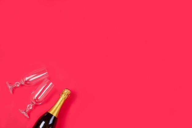 Bottiglia di champagne e due bicchieri di champagne su sfondo rosso.