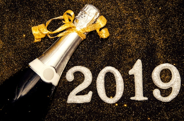 Bottiglia di champagne e numeri di argento 2019 su scintillii dorati in nero. ciao felice anno nuovo