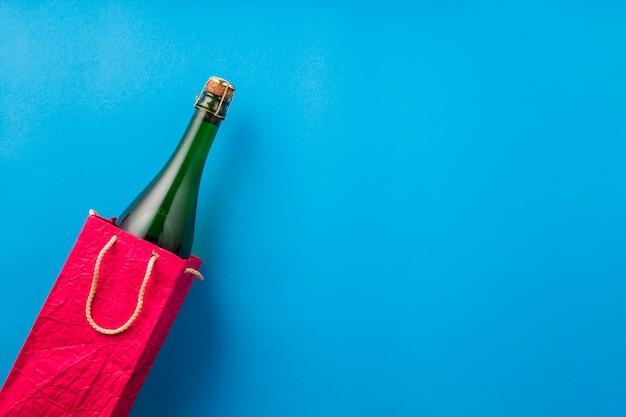 Bottiglia di champagne in sacchetto di carta rosso brillante sulla superficie blu