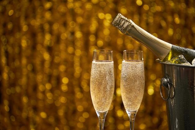 Bottiglia di champagne in un secchio con ghiaccio e due bicchieri di champagne su bokeh dorato