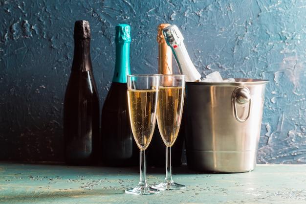 Bottiglia di champagne nel secchio con ghiaccio e bicchieri di champagne