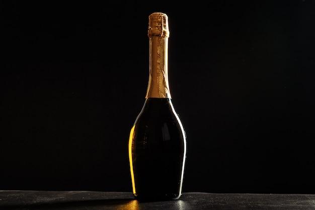 Bottiglia di champagne su sfondo nero.
