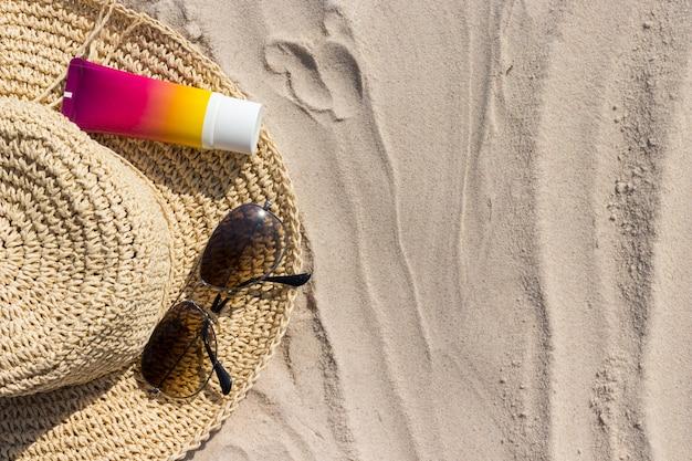 Bottiglia di crema solare con occhiali da sole e panamhat sulla spiaggia, rimedi estivi per la pelle e protezione