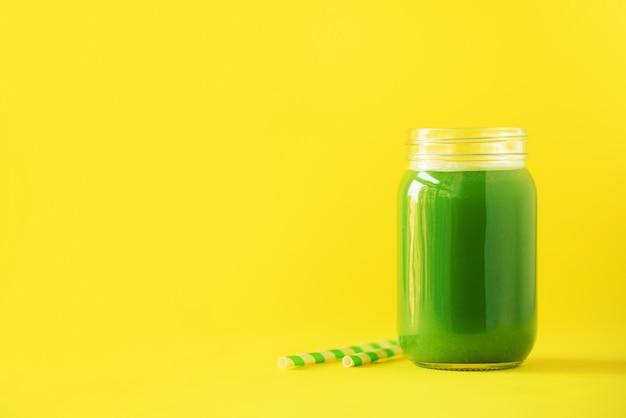 Bottiglia di frullato di sedano verde su sfondo giallo