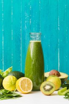 Bottiglia di frullato vista frontale con limone e kiwi