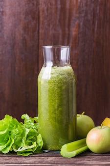 Bottiglia di frullato vista frontale con mela e verdure