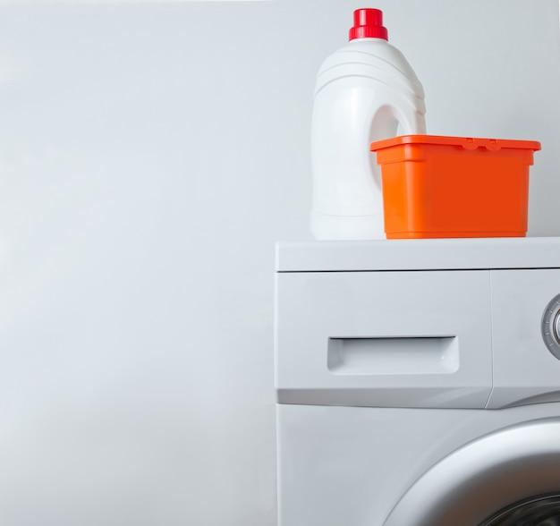 Bottiglia di gel detergente e scatola di polvere sulla lavatrice