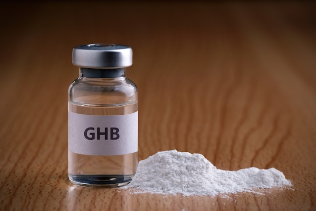 Bottiglia di ghb con polvere di droga su superficie di legno ghb