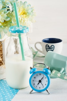 Bottiglia di latte con paglia e sveglia blu