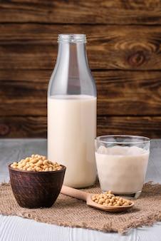 Bottiglia di latte di soia con semi di soia sul tavolo bianco su sfondo di legno scuro