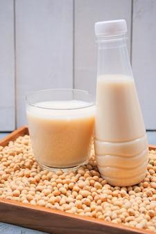 Bottiglia di latte di soia e soia sul tavolo di legno