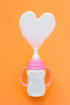 Bottiglia di latte per bambino sull'arancia.