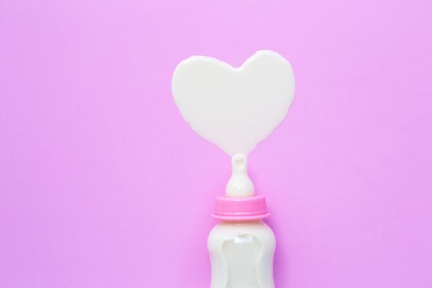 Bottiglia di latte per il bambino sul rosa. forma di cuore di latte