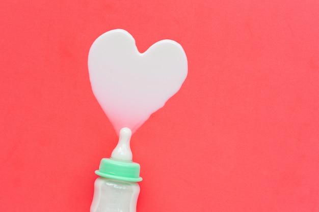 Bottiglia di latte per il bambino sul rosa