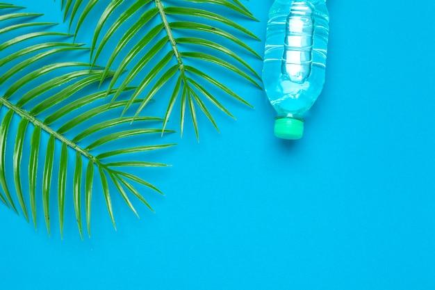Bottiglia di liquido trasparente con foglie di palma tropicale