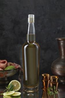 Bottiglia di liquore con mini calici, vaso, limone, sciarpa e foglie di menta