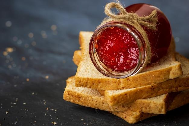 Bottiglia di marmellata di fragole e pane integrale sono impilati su uno sfondo nero.