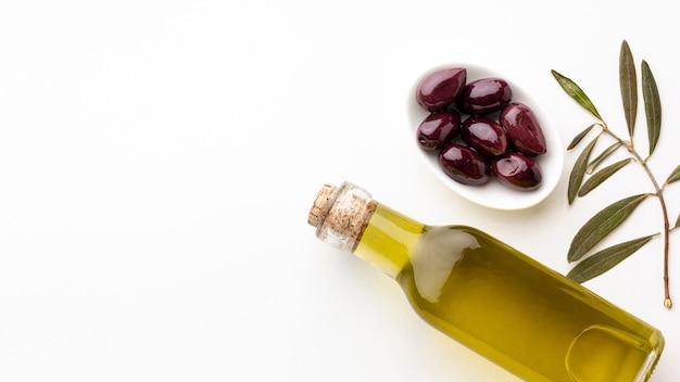 Bottiglia di olio d'oliva con foglie e olive viola con spazio di copia